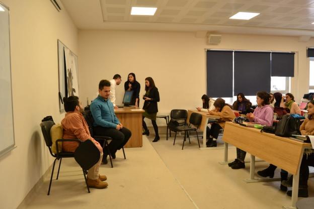 Uğurcan ve Oğuzhan sahnede sandalyede yanyana oturuyorlar. Sahnede bulunan masanın etrafında birkaç kişi bulunuyor. Amfi düzenindeki sıralarda öğrenciler otururken görülmekte.